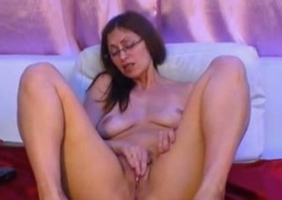 Big-assed milf in glasses fingers her cooch in webcam solo show