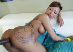 A slut that has hawt tattoos is riding a big black dick on the sofa