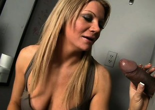 Breasty blond milf with a spicy ass Christina Skye worships a large cock at the gloryhole