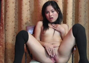 Sweet Oriental strips and fucks her wet crack with a toy