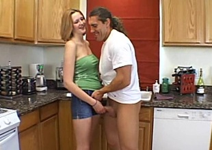 Diminutive amateur babe with natural boobs milking a cock in the kitchen