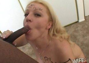 Seductive blonde deepthroats a big black schlong and takes a cumshot