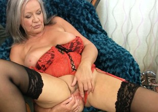 Plumper gray haired granny slips her fingers in her slit and teases