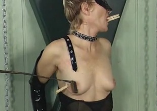 Clothes pins on the tits of a girl in black latex
