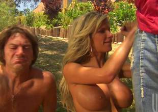 Good looking busty golden-haired gets down on her knees and gives nice deep blowjob to a stranger in front of her husband in the open air. This large titted woman is good at deepthroating