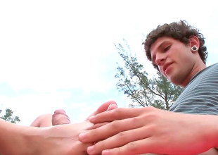 Slim dark brown AJ gives a footjob in a public
