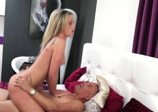 A blonde is with an old dude with a large cock, sucking him off