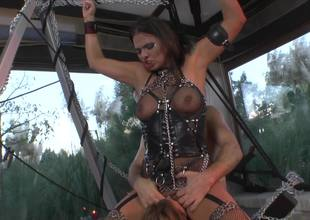 A redhead is with her blond friend and a dude in a domination scene