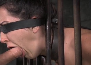 Manacled slave in a cage opens her mouth for face fucking