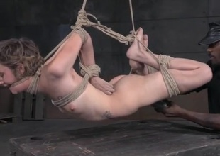 Skinny cutie in a rope bondage suspension suffers abuse