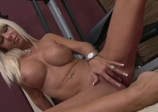 Tanned mommy with big fake tits rubs her slit