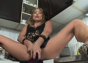 Blonde Milf Tara Romain cooks something up in the kitchen that goes up her ass