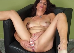 Mature explores her pussy with a pleasurable toy