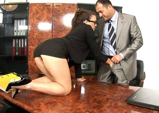A very helpful secretary wears glasses while her boss nails her