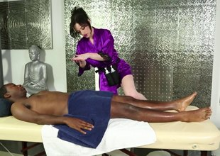 Pale skinned masseuse sucking a black dude's cock on the massage table