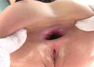A brunette that loves anal is covered with oil and she is screwed