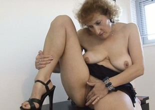 Stacked mature lady lies on the floor satisfying her desires with her skillful fingers