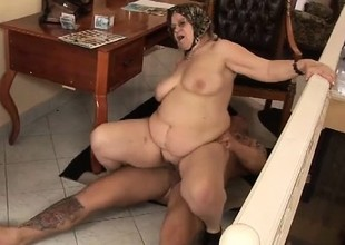 Naughty fat grandma working on the cock of a huge tattooed stud