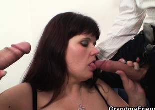 Busty mommy swallows two cocks after photosession