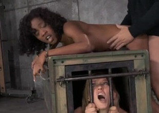 Girl in a cage watches a bound black wench get fucked